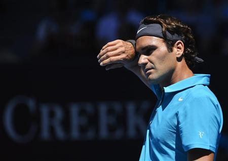 Roger Federer of Switzerland wipes his brow during his men's singles match against Benoit Paire of France at the Australian Open tennis tournament in Melbourne January 15, 2013. REUTERS/Toby Melville