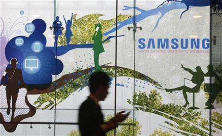 A man using a mobile phone walks past a Samsung Electronics' advertisement in Seoul October 5, 2012. REUTERS/Kim Hong-Ji/Files