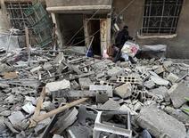 Un hombre recoge sus pertenencias entre los restos de su hogar tras un ataque de la Fuerza Aérea Siria en un barrio de Damasco, ene 16 2013. Al menos 24 personas murieron, en su mayoría soldados del Gobierno de Siria, en tres ataques coordinados con coches bomba ocurridos en la provincia de Idlib, reportó el miércoles un grupo activista, un día después de que unos atentados mataran a más de 87 personas en la Universidad de Aleppo. REUTERS/Goran Tomasevic