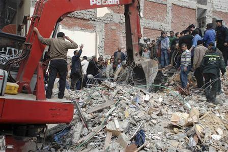 People and rescue workers stand on the rubble of a collapsed building as they search for survivors in Alexandria January 16, 2013. REUTERS/Stinger