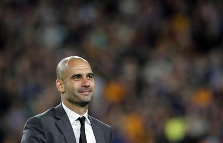 Barcelona's coach Pep Guardiola acknowledges supporters during his last match at Camp Nou stadium in Barcelona May 5, 2012. REUTERS/Albert Gea/Files