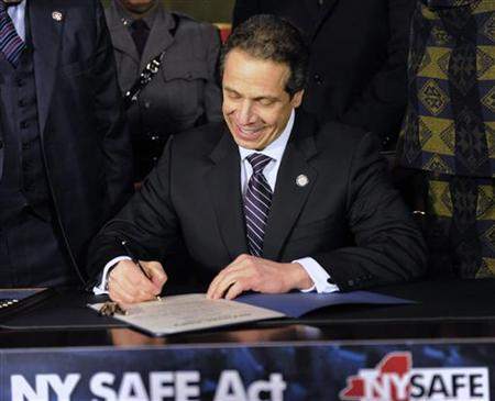 New York Governor Andrew Cuomo signs the New York Secure Ammunition and Firearms Enforcement Act at the Capitol in Albany, New York January 15, 2013. Cuomo on Tuesday signed into law one of the nation's toughest gun-control measures and the first to be enacted since the mass shooting last month at an elementary school in neighboring Connecticut. REUTERS/Hans Pennink