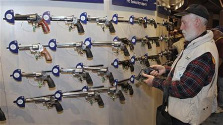 Homer Van Meter, of Rhineland, WI, inspects a revolver during the National Rifle Association's (NRA) 141st Annual Meetings & Exhibits in St. Louis, Missouri, April 13, 2012. REUTERS/Tom Gannam