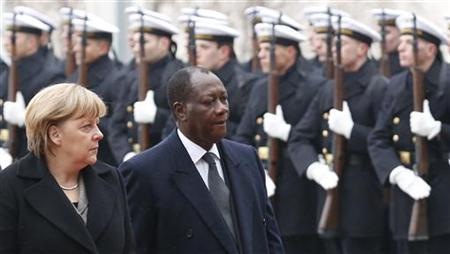 German Chancellor Angela Merkel (L) and Ivory Coast's President Alassane Ouattara inspect the guard of honour during a welcome ceremony before talks in Berlin January 16, 2013. REUTERS/Tobias Schwarz (GERMANY - Tags: POLITICS)