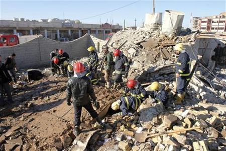 Iraqi civil defence personnel inspect a damaged building after a suicide bomb blast attack in Kirkuk, 250 km (155 miles) north of Baghdad January 16, 2013. The suicide bomber killed 10 people in Iraq's Kirkuk on Wednesday after he detonated his explosive-packed truck outside a Kurdish party office in the city caught in a dispute between Baghdad and the country's autonomous Kurdistan, officials said. REUTERS/Ako Rasheed (IRAQ - Tags: POLITICS CIVIL UNREST)