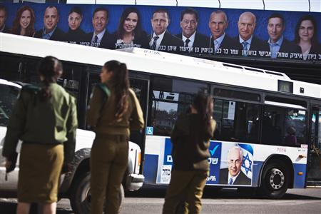 Israeli soldiers wait to cross a road in Tel Aviv as a bus with a campaign poster depicting Israel's Prime Minister Benjamin Netanyahu drives past a Labour party campaign banner (top) January 16, 2013. REUTERS/Nir Elias