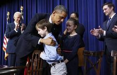 Il presidente Usa Barack Obama alla Casa Bianca abbraccia un bambino dopo aver firmato una serie di proposte per ridurre e controllare maggiormente la diffusione di armi da fuoco in Usa. REUTERS/Jason Reed