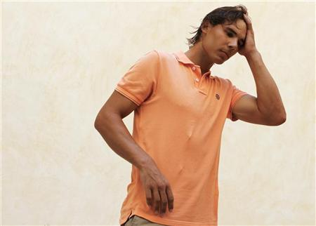 Spain's Rafael Nadal combs his hair back with his hand between television interviews, during which he detailed reasons for pulling out of the U.S. Open, in Palma de Mallorca, on the island of Mallorca August 17, 2012. REUTERS/Enrique Calvo