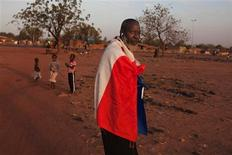 En las remotas ciudades desérticas del norte de Mali, los civiles cansados del violento dominio de los rebeldes islamistas esperan que las tropas francesas puedan expulsarles, pero temen quedarse atrapados en el fuego cruzado conforme los combatientes intentan mezclarse con la población local. En la imagen, Yacuba Konate, de 56 años, lleva uan bandera francesa para mostrar su apoyo a la intervención militar francesa en Mali, en la capital del país, Bamako, el 13 de enero de 2013. REUTERS/Joe Penney