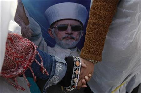Women supporters of Sufi cleric and leader of the Minhaj-ul-Quran religious organisation Muhammad Tahirul Qadri hold hands during his speech on their third day of protests in Islamabad January 16, 2013. REUTERS/Akhtar Soomro