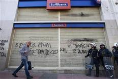 Imagen de archivo de una persona junto a unos policías frente a una sucural del banco Eurobank en Atenas, mar 21 2012. El Fondo Monetario Internacional (FMI) aprobó el miércoles el desembolso de un préstamo de 3.240 millones de euros (4.310 millones de dólares) a Grecia, tras meses de incertidumbre respecto al doloroso programa de austeridad y reformas del país. REUTERS/John Kolesidis