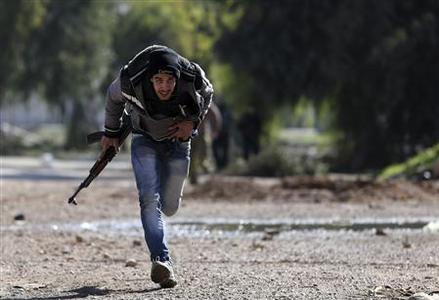 A Free Syrian Army fighter runs for cover at a suburb of Damascus January 16, 2013. REUTERS/Goran Tomasevic
