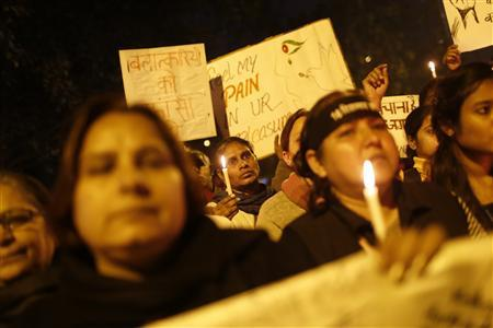 Demonstrators hold candles and placards during a candlelight march for a gang rape victim, who was assaulted in New Delhi January 16, 2013. REUTERS/Adnan Abidi
