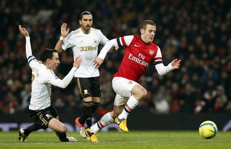 Arsenal's Jack Wilshere (R) runs past Swansea City's Chico Flores (C) and Leon Britton during their FA Cup third round replay soccer match at the Emirates Stadium in London January 16, 2013. REUTERS/Suzanne Plunkett