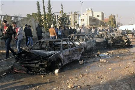 Damaged cars are seen at the site where two explosions rocked the University of Aleppo in Syria's second largest city, January 15, 2013. REUTERS/George Ourfalian