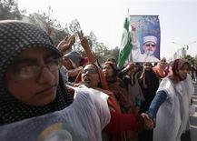 Women supporters of Sufi cleric and leader of the Minhaj-ul-Quran religious organisation Muhammad Tahirul Qadri link their hands during his speech on their third day of protests in Islamabad January 16, 2013. REUTERS/Akhtar Soomro
