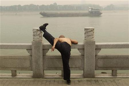A man stretches his leg on the bank of the Han River as a ship passes by amid thick haze in Wuhan, Hubei province June 15, 2012. REUTERS/Stringer/Files
