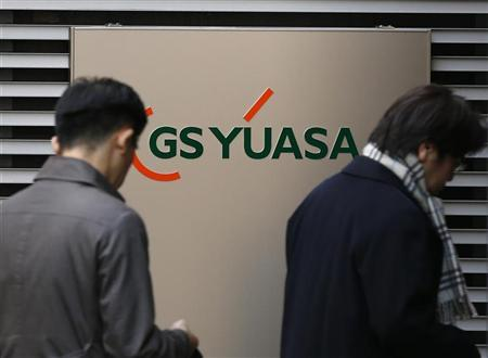 People walk past the signboard of GS Yuasa Corp, which makes batteries for the Dreamliner, at its headquarters in Tokyo January 16, 2013. REUTERS/Kim Kyung-Hoon