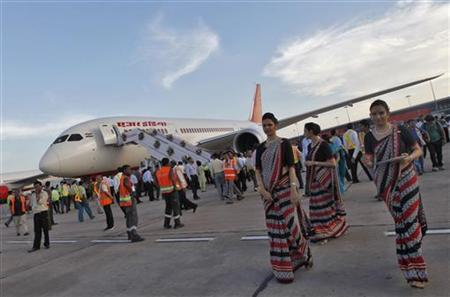 Air hostesses walk next to the parked Air India's Boeing 787-800 Dreamliner upon its arrival at the airport in New Delhi September 8, 2012. REUTERS/Mansi Thapliyal/Files