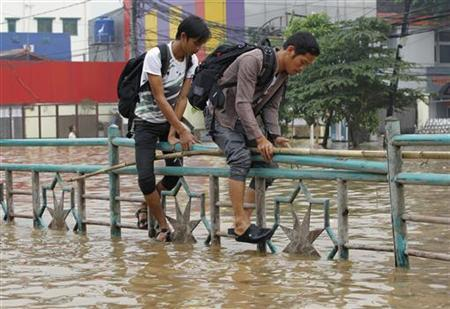 Two men walk through a fence to cross a flooded road in Jakarta January 16, 2013. REUTERS/Enny Nuraheni