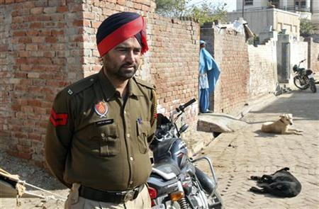 A policeman stands guard as a woman covers her face near the house of a gang rape victim at village Badshahpur in Punjab January 10, 2013. REUTERS/Ajay Verma