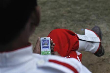 A member of a brass band watches a video clip on his mobile phone as he waits to perform at a wedding procession in New Delhi November 24, 2012. REUTERS/Mansi Thapliyal/Files