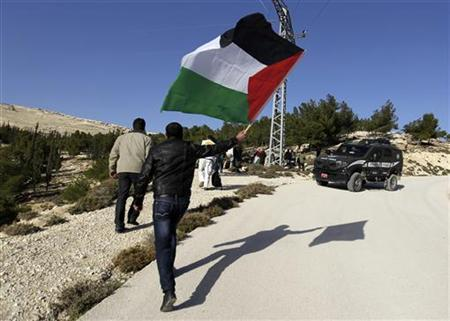 A Palestinian protester holds a flag as he arrives at an area known as ''E1'', which connects the two parts of the Israeli-occupied West Bank outside Arab suburbs of East Jerusalem January 15, 2013. REUTERS/Ammar Awad