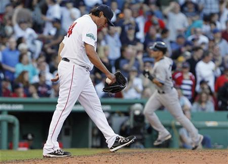 Boston Red Sox pitcher Vicente Padilla (L) reacts as New York Yankees' Nick Swisher (R) rounds the bases after hitting a grand slam during the seventh inning of American League MLB baseball action at Fenway Park in Boston, Massachusetts April 21, 2012. REUTERS/Jessica Rinaldi
