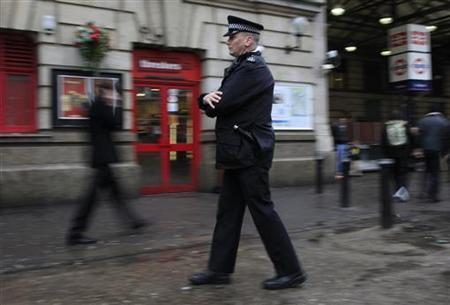 A police officer walks outside Victoria station central in London January 7, 2011. REUTERS/Stefan Wermuth