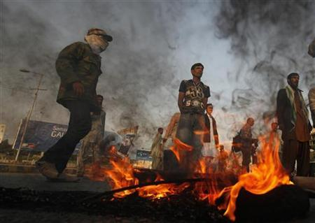 Supporters of Pakistan People's Party (PPP) stand near burning tyres to block a road during a protest against the Supreme Court's decision to arrest Prime Minister Raja Pervez Ashraf in Karachi January 16, 2013. REUTERS/Athar Hussain