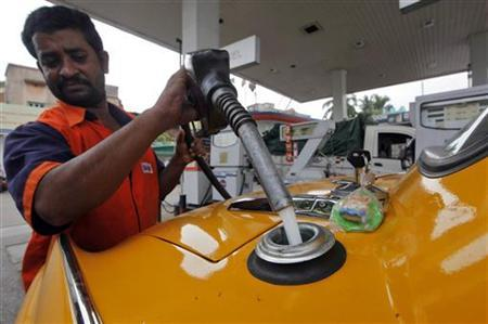 An employee fills an iconic yellow ambassador taxi with diesel at a fuel station in Kolkata June 24, 2011. REUTERS/Rupak De Chowdhuri/Files