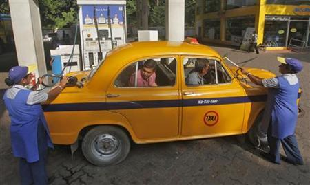 An employee fills a taxi with diesel as her colleague clean the windows of the car at a fuel station in Kolkata September 19, 2012. REUTERS/Rupak De Chowdhuri
