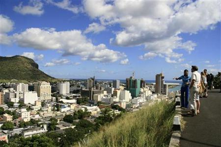 A tour guide stands with a group of tourists at a viewpoint overlooking Port Louis June 6, 2008. REUTERS/Ed Harris/Files