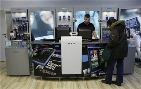 A customer looks at an advertising for Nokia Lumia smartphone in a Nokia shop in Warsaw, January 11, 2013. REUTERS/Kacper Pempel (POLAND - Tags: BUSINESS TELECOMS)