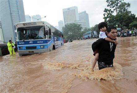A man carries his son across a flooded area at the business district in Jakarta January 17, 2013. REUTERS/Supri