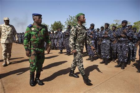 Ivory Coast army chief-of-staff Soumaila Bakayoko (L) and Malian army chief-of-staff Ibrahima Dahirou Dembele (C) inspect Malian troops at an air base in Bamako, Mali January 16, 2013. REUTERS/Joe Penney