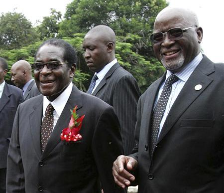 Zimbabwe's President Robert Mugabe (L) walks with his newly sworn-in Vice President John Nkomo (R) at the State House in the capital Harare in this December 14, 2009 file photo. Zimbabwean Vice-President Nkomo died in South Africa on January 17, 2013 after years of battling cancer, a Zimbabwean political source said, removing a potential successor to ageing Mugabe, who has his own health problems. Nkomo, 78, was nominated for the joint number two position alongside Joice Mujuru two years ago after a fractious meeting of the southern African nation's ruling ZANU-PF party. REUTERS/Philimon Bulawayo/Files