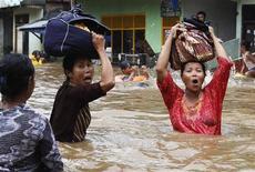 Mulheres fogem de região inundada em Jacarta. Intensas chuvas das monções causaram grandes inundações em vários pontos da capital da Indonésia, levando ao fechamento de várias empresas e órgãos públicos. 17/01/2013 REUTERS/Enny Nuraheni