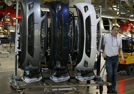 A worker passes bumper assemblies for Astra cars on the production line at the Vauxhall Motors plant in Ellesmere Port, northern England May 17, 2012. REUTERS/Phil Noble