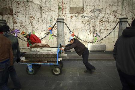 A man pushes a trolley loaded with scrap metals to sell, in the Andalusian capital of Seville January 10, 2013. REUTERS/Marcelo del Pozo