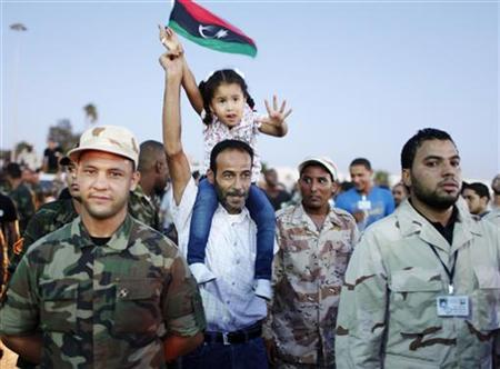 A protester holds his daughter surrounded by army soldiers as they attend a march in Benghazi city, September 21, 2012. REUTERS/Asmaa Waguih