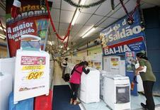 Consumidores olham máquinas de lavar em loja das Casas Bahia, em São Paulo, em dezembro de 2009. Índice Geral de Preços-10 (IGP-10) registrou elevação de 0,42 por cento em janeiro, após alta de 0,63 por cento em dezembro, influenciado principalmente pela desaceleração dos preços no atacado. 04/12/2009 REUTERS/Paulo Whitaker