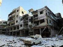 """Más de 100 personas murieron fusiladas, acuchilladas y posiblemente quemadas en la ciudad siria de Homs esta semana, en un hecho descrito por un grupo activista como una """"masacre"""" perpetrada por fuerzas leales al presidente Bashar el Asad. En la imagen, un coche dañado y edificios destruidos cubiertos de nieve en Homs, el 10 de enero de 2013. REUTERS/Yazan Homsy"""