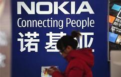 Mulher passa em frente a propaganda da Nokia em Shenyang, na China. A fabricante finlandesa de celulares vai eliminar mais de 1.000 postos de trabalho na área de tecnologia da informação como parte do plano de reestruturação para estancar a sangria financeira. 06/12/2012 REUTERS/Stringer