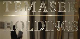 A staff member is reflected in a Temasek Holdings logo at their headquarters before the presentation of Temasek's annual review in Singapore September 17, 2009. REUTERS/Vivek Prakash