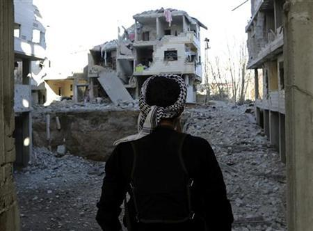 A Free Syrian Army fighter looks at houses destroyed by the Syrian Air force at a suburb of Damascus January 16, 2013. REUTERS/Goran Tomasevic (SYRIA - Tags: POLITICS CIVIL UNREST)