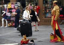 La patronal de las empresas turísticas españolas Exceltur dijo el jueves que el sector turístico español registrará una caída acumulada del orden del 2,6 por ciento durante el periodo 2012-2013 antes de retomar la senda de crecimiento el próximo año. En la imagen, unos turistas pasan junto a un hombre vestido de torero en Madrid, el 2 de octubre de 2012. REUTERS/Sergio Pérez