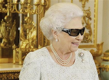 Britain's Queen Elizabeth watches a preview of her Christmas message with a pair of 3D glasses, studded with Swarovski crystals in the form of a ''Q'', at Buckingham Palace in central London in a photo released December 24, 2012. REUTERS/John Stillwell/Pool