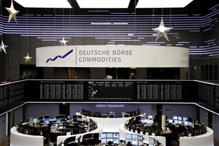 Traders are pictured at their desks in front of the DAX board at the Frankfurt stock exchange January 4, 2013. REUTERS/Remote/Joachim Herrmann