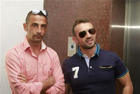Italian sailors Massimiliano Latorre (L) and Salvatore Girone wait to board an elevator to reach the police commissioner's office in Kochi December 18, 2012. REUTERS/Sivaram V/Files